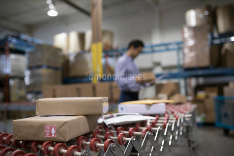 Male warehouse manager checking packages on production line conveyor beltの写真素材 [FYI02325827]