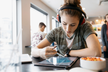 High school girl student with headphones using stylus, drawing on digital tablet in cafeの写真素材 [FYI02325837]