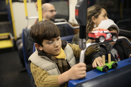 Boy playing with toys on busの写真素材 [FYI02325865]