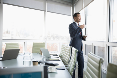 Thoughtful businessman drinking tea, looking out conference room windowの写真素材 [FYI02325869]