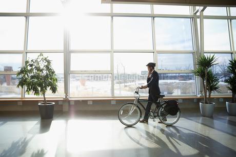 Businessman commuter in helmet walking bicycle in sunny office lobbyの写真素材 [FYI02325893]