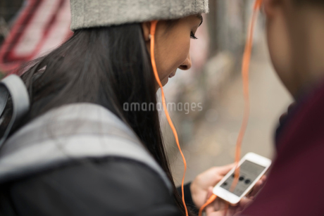 Close up young couple sharing headphones, listening to music with smart phoneの写真素材 [FYI02325914]