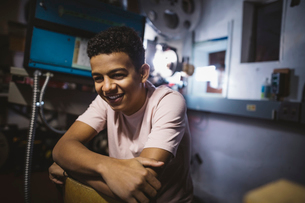 Smiling, laughing mixed race tween boy projectionist in movie theaterの写真素材 [FYI02325919]
