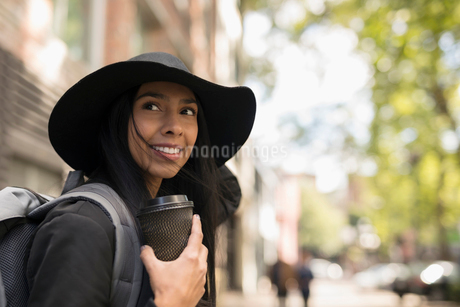 Smiling young woman in hat drinking coffee on streetの写真素材 [FYI02325920]