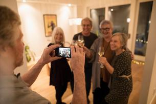 Senior man with camera phone photographing friends drinking wine, enjoying social gatheringの写真素材 [FYI02325950]