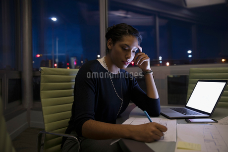 Focused, dedicated female architect working late at laptop, editing blueprints in dark conference roの写真素材 [FYI02325959]