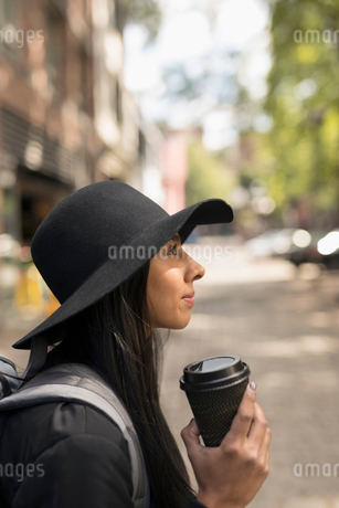 Profile pensive young woman wearing fedora and drinking coffee on street, looking awayの写真素材 [FYI02325960]