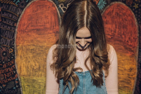 Smiling, shy Caucasian brunette tween girl against wall with chalk wingsの写真素材 [FYI02325965]