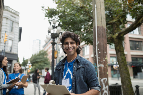 Portrait smiling, confident political young man canvassing with clipboard on urban sidewalkの写真素材 [FYI02325976]