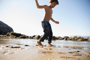 Bare chested boy walking in wet sand on sunny ocean beachの写真素材 [FYI02325988]