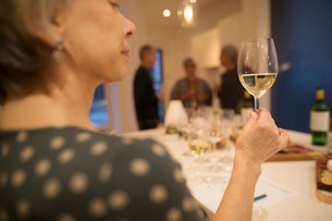 Senior woman examining and rating white wine at wine tasting partyの写真素材 [FYI02326072]