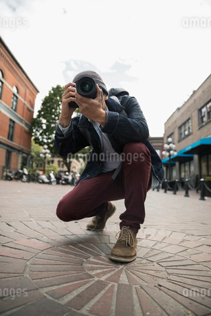 Man with digital camera photographing on urban streetの写真素材 [FYI02326073]