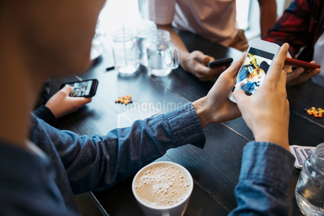 Tween boy using camera phone and drinking coffee at cafe tableの写真素材 [FYI02326075]