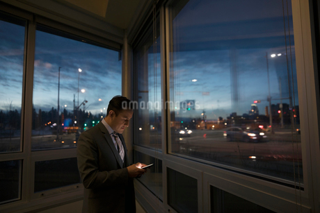 Businessman texting with smart phone at dark office window overlooking cityの写真素材 [FYI02326076]