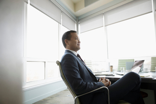 Confident, attentive businessman listening in conference room meetingの写真素材 [FYI02326080]