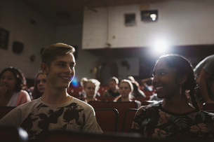 Smiling tween couple watching movie in dark movie theaterの写真素材 [FYI02326083]