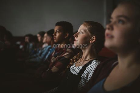 Serious tween girl watching movie in dark movie theaterの写真素材 [FYI02326119]