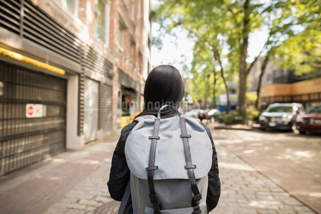 Young woman with backpack on urban streetの写真素材 [FYI02326131]