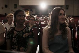 Tween girl friends watching movie in dark movie theaterの写真素材 [FYI02326136]