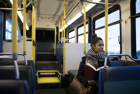 Woman commuter reading book on busの写真素材 [FYI02326154]
