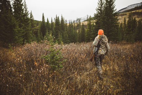 Female hunter in camouflage and orange beanie carrying hunting rifle in remote fieldの写真素材 [FYI02326162]