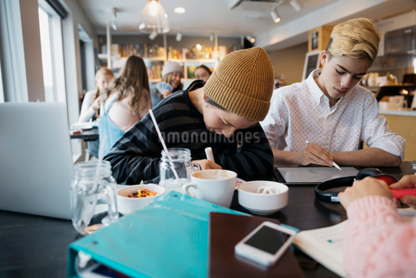 Focused high school boy students studying at cafe tableの写真素材 [FYI02326174]