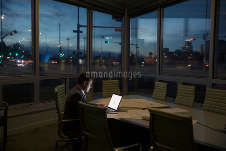 Dedicated male architect working late at laptop in dark conference roomの写真素材 [FYI02326179]