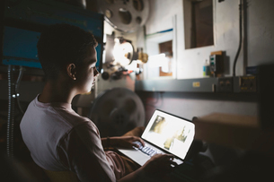 Mixed race tween boy projectionist using laptop in dark movie theaterの写真素材 [FYI02326185]