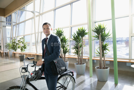 Portrait confident businessman commuter with bicycle in office lobbyの写真素材 [FYI02326196]