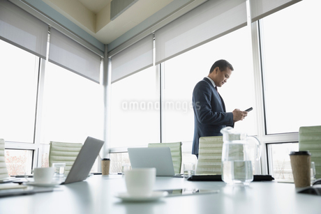 Businessman texting with smart phone at conference room windowの写真素材 [FYI02326214]