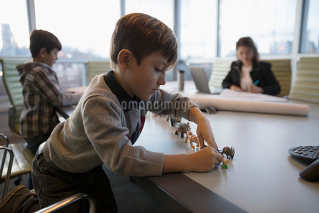 Boy playing with toys on conference room table with mother architect working in backgroundの写真素材 [FYI02326225]