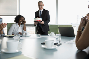 Businessman serving birthday cake to surprised businesswoman in conference roomの写真素材 [FYI02326236]