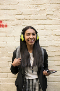 Portrait confident smiling young woman listening to music with headphones and smart phoneの写真素材 [FYI02326240]