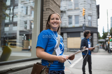Smiling political young woman canvassing with clipboard on urban sidewalkの写真素材 [FYI02326249]