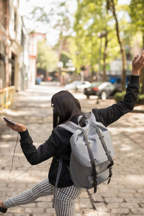Playful young woman with backpack dancing, listening to music with headphones and smart phone on urbの写真素材 [FYI02326263]