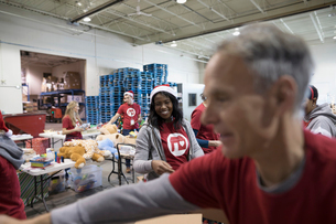 Female volunteer in Santa hat filling Christmas donation boxes in warehouseの写真素材 [FYI02326286]