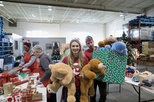 Portrait smiling female volunteer carrying teddy bear toys in warehouseの写真素材 [FYI02326303]