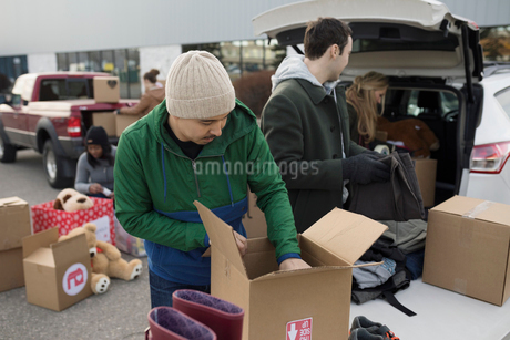 Young male volunteer filling donation box in parking lotの写真素材 [FYI02326306]