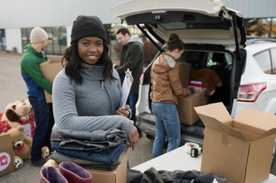 Portrait smiling, confident young female volunteer loading donations into car in parking lotの写真素材 [FYI02326309]