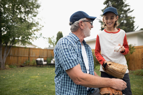 Grandfather and grandson playing baseball in backyardの写真素材 [FYI02326345]