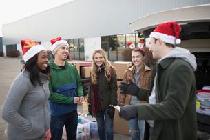Young adult volunteers in Santa hats meeting in parking lotの写真素材 [FYI02326354]
