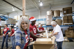 Female volunteer filling Christmas donation boxes in warehouseの写真素材 [FYI02326359]