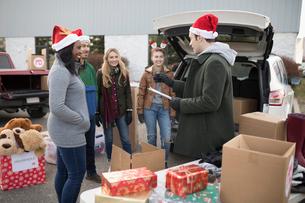 Young adult volunteers in Santa hats meeting in parking lotの写真素材 [FYI02326369]