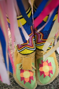 Close up vibrant, multicolor moccasins on feet of Native American Indian girlの写真素材 [FYI02326392]