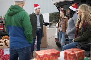 Young adult volunteers in Santa hats meeting in parking lotの写真素材 [FYI02326395]