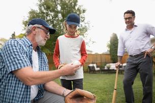 Multi-generation family men playing baseball in backyardの写真素材 [FYI02326403]
