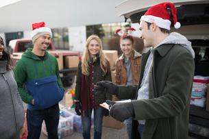 Young adult volunteers in Santa hats meeting in parking lotの写真素材 [FYI02326418]