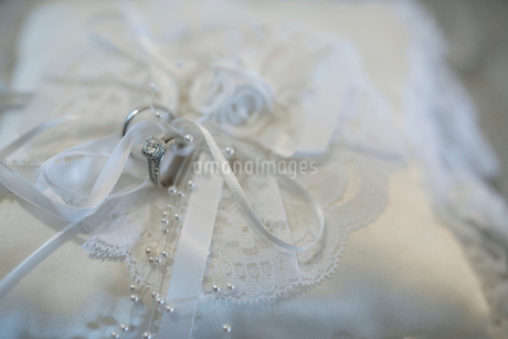 Close up still life wedding rings tied to white satin wedding pillowの写真素材 [FYI02326432]