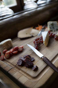 Still life cheese board with dried salami, tomatoes and grapesの写真素材 [FYI02326454]