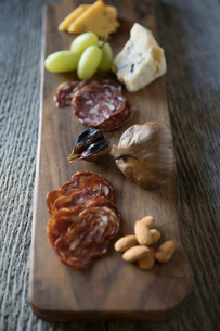 Close up still life charcuterie featuring cheese, salmi, nuts and fruit on rustic wooden boardの写真素材 [FYI02326463]